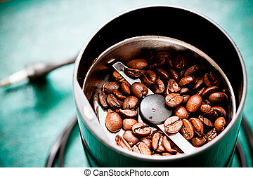 Electrical coffee-mill machine with roasted coffee beans on the green tabletop with top cover removed