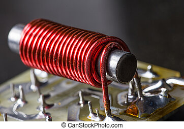 An electrical coil or component showing wire wrapping and iron core