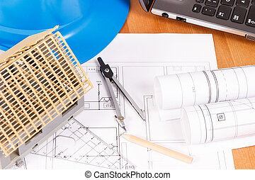 Electrical diagrams, accessories for engineer jobs and house under construction on desk, building home concept
