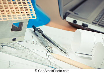 Electrical diagrams, accessories for engineer jobs and small toy house under construction on desk
