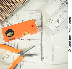 Electrical diagrams, orange work tools for engineer jobs and house under construction, building home concept