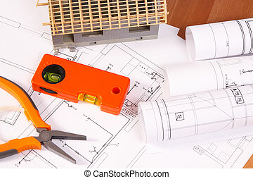 Electrical diagrams, orange work tools for engineer jobs and house under construction
