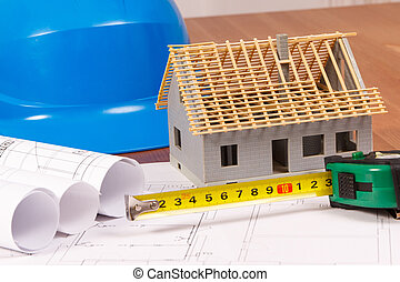 Electrical drawings, tape measure, blue helmet for engineer jobs and house under construction, building home concept