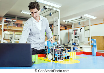 Electrical engineer programming a robot during robotics class