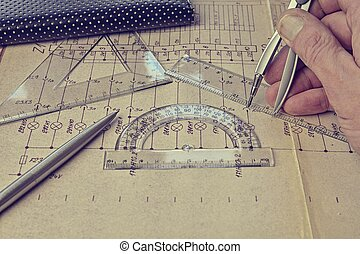Electrical engineer workplace - electrotechnical project, rulers, and divider compass. Construction and electrotechnology concept. Engineering tools. Circuit diagram on background. Retro haze.