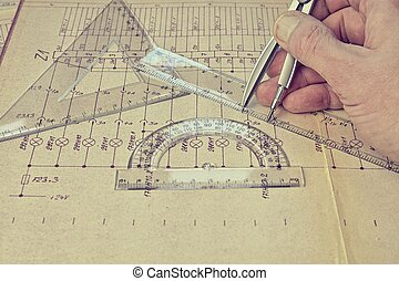 Electrical engineer workplace - electrotechnical project, rulers, and divider compass. Construction and electrotechnology concept. Engineering tools. Circuit diagram on background. Retro haze. Construction projects. Planning.
