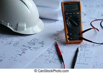 Electrical power engineer's work place with helmet, multimeter and drawings.