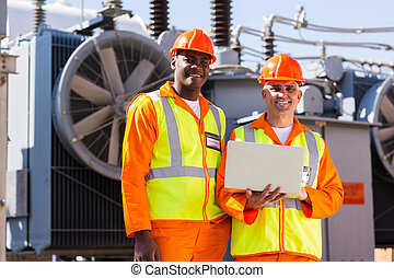 electrical engineers with laptop in front of transformer