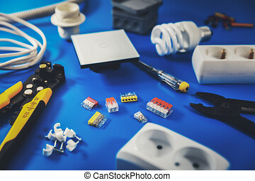 electrical installation - electrician tools and equipment on blue background