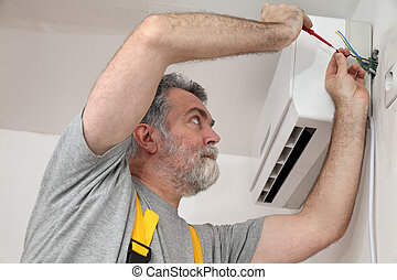 Electrical installation of air conditioner, electrician at work
