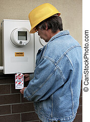Electrical lock out - Electrician places a lock out tag on...