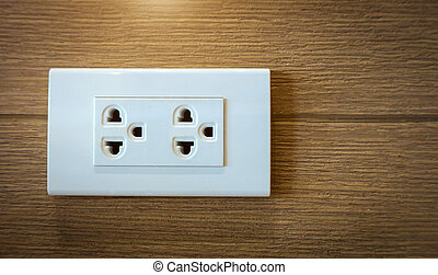 Electrical plug socket on wooden wall