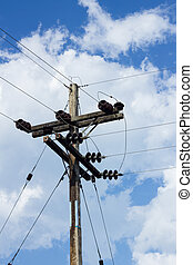 electrical post by the road with power line cables, against blue sky with cloud