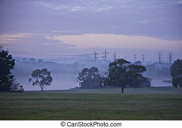 Electrical Pylons - Electrical pylons in morning mist near a...