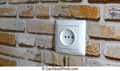 Electrical socket burns on wall in house. Short circuit and fire hazard. Maybe power grid is overloaded or equipment turned out to be of poor quality. Selective focus. Close-up.