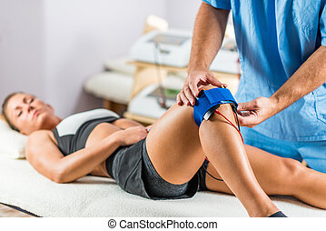 Electrical stimulation in physical therapy. Therapist positioning electrodes onto a patient's knee