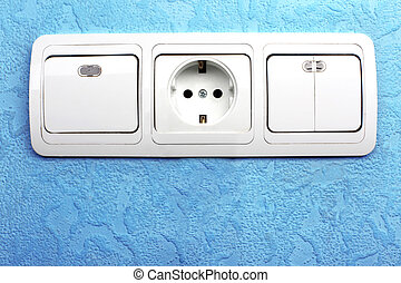 Electrical switch and plug in blue wall