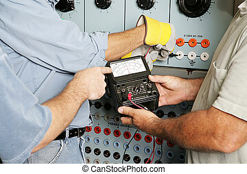Team of actual electricians testing the voltage on an industrial power distribution center. All work is being performed according to industry code and safety standards. Note to inspector: the word OHMS on the meter is a unit of measurment, not a trademark