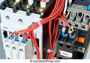 Electrical wires or cables are connected to magnetic starters or contactors.
