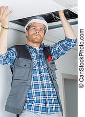 electrical worker wiring in ceiling