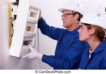 Electrician and apprentice mounting electric meter