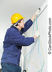 Electrician at cable wiring work