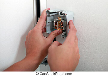 electrician attaching electrical outlet to wall