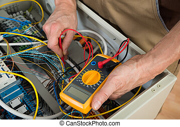 Close-up Of A Electrician Checking Fuse Box With Multimeter