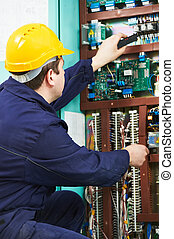 Electrician checking current at power line box - One...