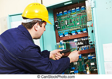 Electrician checking current at power line box - One ...