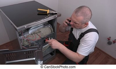 Electrician checking electric cooker and talking on phone