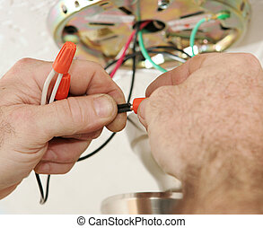 A closeup of an electrician's hands as he connects wires using a wire-nut. All work is being performed to code by a licensed master electrician.