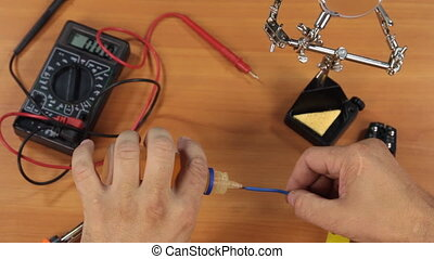 Electrician covers the tinned copper wire with a soldering...