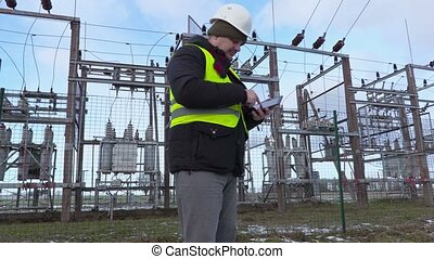 Electrician engineer take pictures on tablet near substation in winter