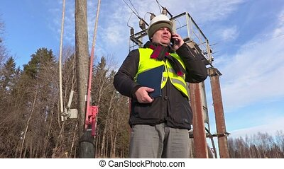 Electrician engineer using smart phone at transformer