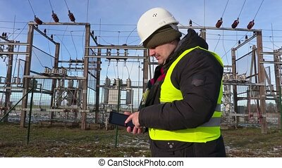 Electrician engineer using tablet near substation in winter