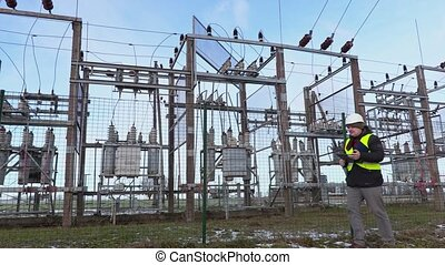 Electrician engineer writing and walking near substation in...