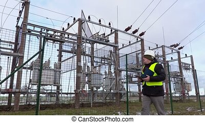 Electrician engineer writing near substation