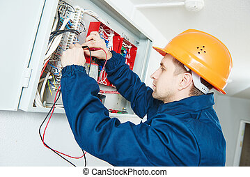 electrician examining current voltage with screwdriver ...