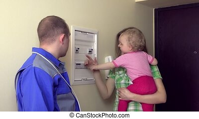 Electrician explain for housewife woman with child how to use circuit breaker