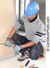 Electrician fixing wall electrics