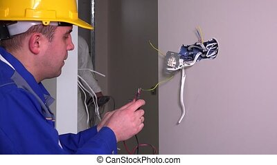 Electrician guy checking socket voltage using multimeter in...