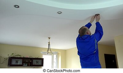 Electrician guy installing or replacing a halogen spot light lamp into ceiling at client home.