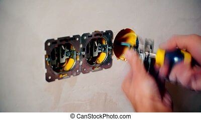Electrician hands install electrical wall sockets