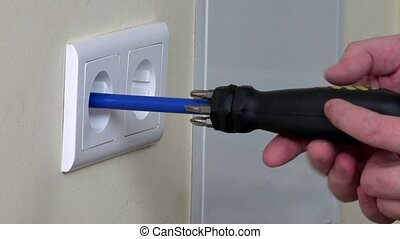 Electrician hands installing electrical wall sockets -...