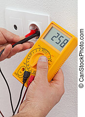 Electrician hands measuring voltage in electrical outlet - closeup