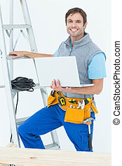 Electrician holding laptop by step ladder