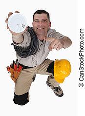 Electrician holding smoke alarm
