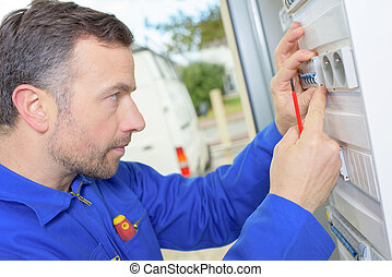 Electrician inspecting a fusebox
