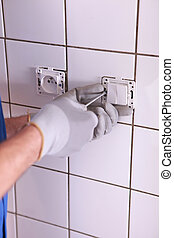 Electrician installing electrical outlet